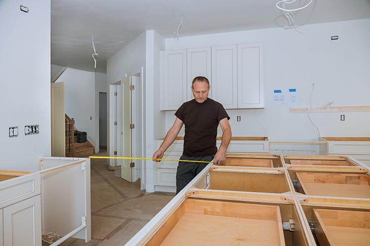 Contractor measuring distance between kitchen cabinets during install